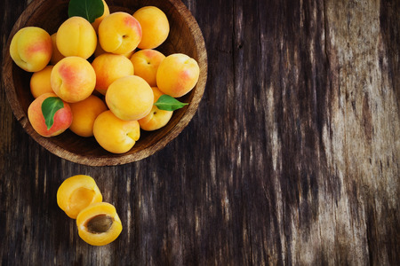 ripe apricots in a wooden bowl on the old wooden background. top view. copy space background
