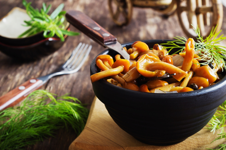 salted: delicious marinated mushrooms in a bowl on the old wooden background. forest gifts. selective focus Stock Photo