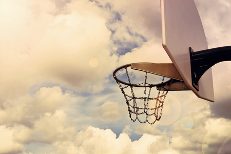 playground basketball: basketball hoop against the background of a cloudy sky. toned photo. street basketball. copy space background