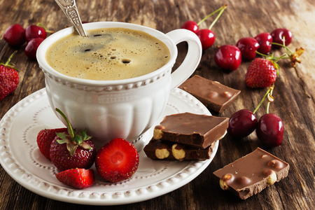 cup of freshly brewed coffee, chocolate and fruit on the old wooden background. rustic style. selective focus Stock Photo