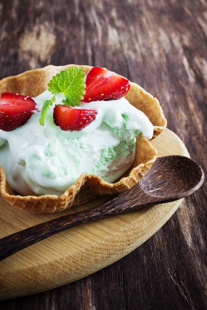 peppermint cream: homemade peppermint ice cream with waffles on a wooden background. selective focus
