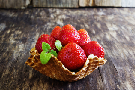 diet product: ripe strawberries in a waffle basket on an old wooden background. rustic style. health and diet product. selective focus. Stock Photo