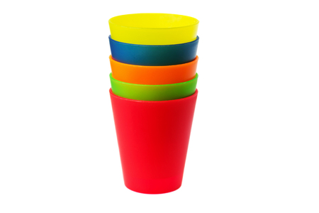 colorful plastic cups of lemonade on a white background. utensils for a picnic and travel