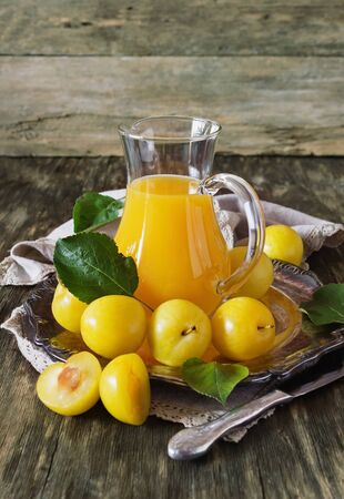 plum: Yellow plum juice in a glass jug and ripe yellow plum on a vintage wooden table. Bio healthy food and drink. Organic diet. Toned image
