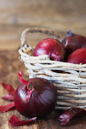 close up of onions in a basket: Ripe red onions in a basket on a vintage wooden background. Close-up. Bio healthy vegetables. Selective focus Stock Photo