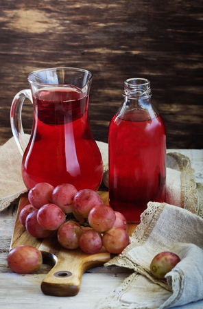 Fresh grape juice in a glass pitcher and ripe berries on the table. Rustic style. Health and diet food. Selective focus Stock Photo