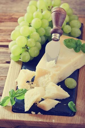 Fresh parmesan cheese and ripe grapes on a table. Tinted image. Health and diet food. Selective focus Stock Photo