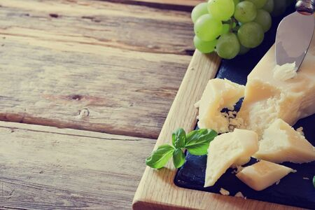 Fresh parmesan cheese and ripe grapes on a table. Tinted image. Health and diet food. Selective focus. Copy space for you text