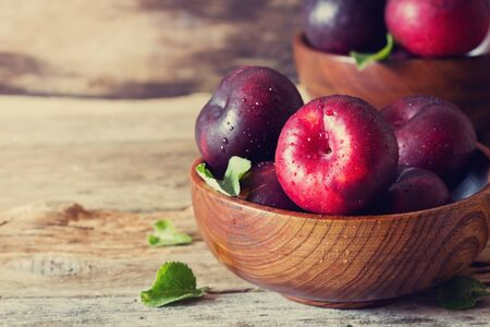 Ripe organic plums in a wooden bowl. Health and diet food. Selective focus. Toned image Stock Photo