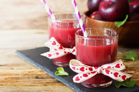 Useful plum juice in a glass on a wooden background. Healthy and diet drink. Selective focus Stock Photo