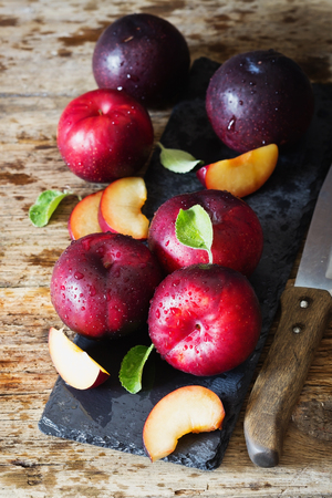 Ripe organic plums on a vintage table. Rustic style. Health and diet food .  Selective focus