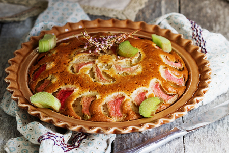 Traditional homemade rhubarb pie in a dish on the table. Tasty breakfast. Selective focus Stock Photo