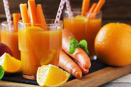 Fruit and vegetable juice in glasses and fresh fruits and vegetables on a wooden background. Healthy eating and healthy lifestyle. Stockfoto