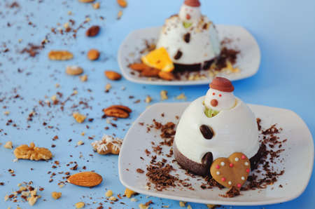 Ice cream background in the shape of two edible snowmen on white plates close up. Top view. Creative idea for Christmas and New Year festive desserts. Funny food idea for kids.