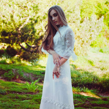 Portrait of young attractive woman in long white wedding dress in spring garden with blooming trees. Spring background. Wedding concept. Greeting card.
