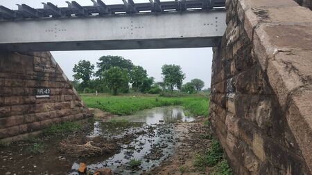 Old railway bridge in india with green grass and stream under in it