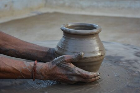 Hands working on pottery wheel and making a pot