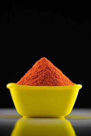 Red chili powder in yellow bowl on dark background