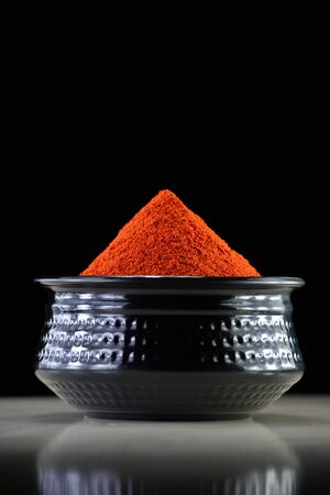 Red chili powder in black bowl on dark background