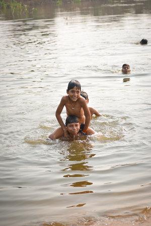 TIKAMGARH, MADHYA PRADESH, INDIA - NOVEMBER 13, 2019: Indian village boys swimming in the fresh river water.