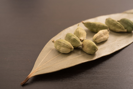 cinnamomum: green cardamom in dried Indian bay leaves on a black background