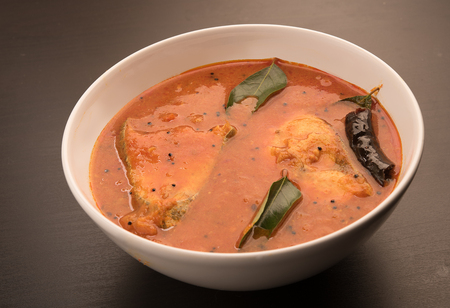 kerala culture: spicy and hot king fish curry with green curry leaf on a black background