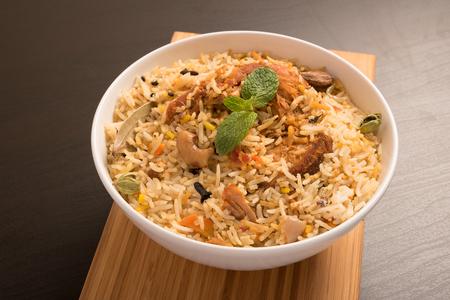 pannel: Yummy delicious chicken biryani in a white round bowl
