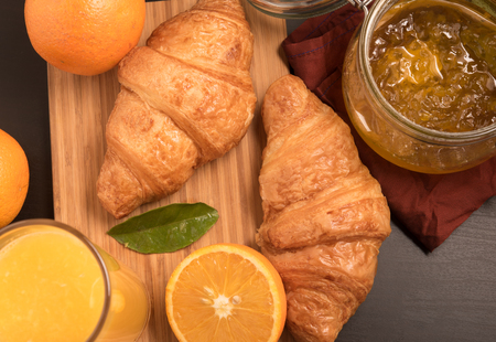 valencia orange: top view of fresh orange juice in a glass with Croissant and jam Stock Photo