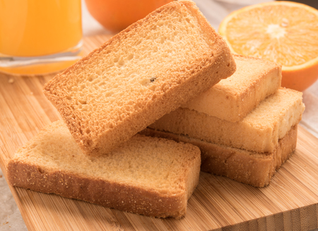 rusk: wheat rusk in a wooden panel with orange and orange juice