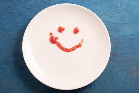 motivated: Smile symbol drawn with ketchup on white plate