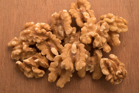 shelled: Big shelled walnuts on a wooden background Stock Photo