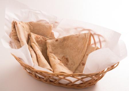 atta: chapati in basket on white background Stock Photo