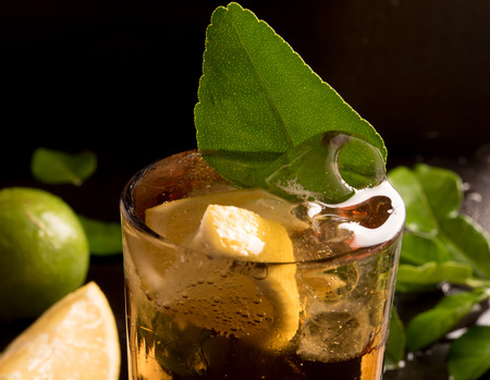 carbonic: glass of cola or coke with ice cubes, lemon slice and mint