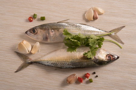 shinning leaves: indian mackerel fish garnished with coriander leaf , garlic and slice of red and green chilli pepper