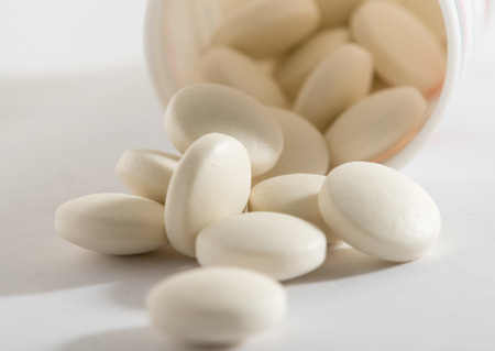 pilule: Small medicine tablets (or pills) spilling out from the bottle