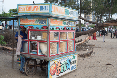 pani: CALICUT, INDIA - JULY 30, 2015: Young men selling local snacks at stall near Calicut beach side of Kerala India Editorial
