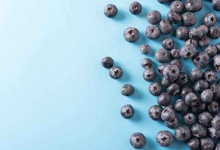 strewed: Blueberry border design. Ripe and juicy fresh picked bilberries close up. Copyspace for your text