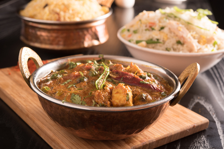paneer: Paneer Butter Masala in a brass bowl on a wooden panel
