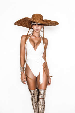 Elegant woman in the white bikini and big hat on the sun-tanned slim and shapely body is posing on white background - Image