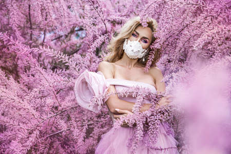 Fashion portrait of young woman wearing a face mask and pink clothes, in a flowering garden Pandemic, virus, coronavirus, Covid-19 masked girl. Spring and summer fashion, model in a mask.