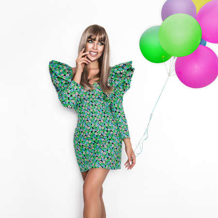 Fashion. Beautiful model in floral summer dress, long hair, makeup. Happy girl with balloons. Pretty blonde woman in fashion look, trendy hairstyle, summertime outfit.