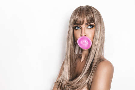 Sexy young girl on white background with chewing gum. Summer fashion. Bubble gum girl concept.