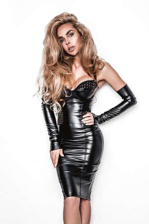 Glamor stylish beautiful young model in black latex clothing isolated on white background. Beauty stylish blonde woman posing in studio. 版權商用圖片