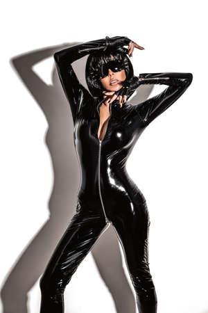 Glamor stylish beautiful young model in black latex clothing isolated on white background. Beauty stylish brunette woman posing in studio. 版權商用圖片