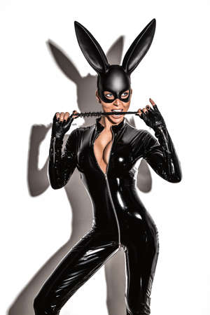 Sexy blonde beautiful woman posing in latex costume and black bunny mask on white background. Easter bunny concept. 版權商用圖片