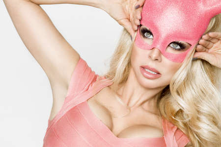 Beautiful sexy, young woman in halloween pink costume and pink mask, standing on white background