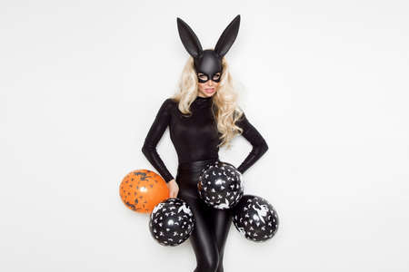 Beautiful young woman in Halloween bunny costume, standing on white background and holding balloons Archivio Fotografico