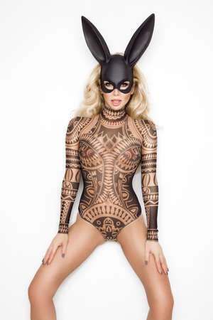 Beautiful young woman in Halloween, tattoo costume and black bunny mask, standing on white background Archivio Fotografico