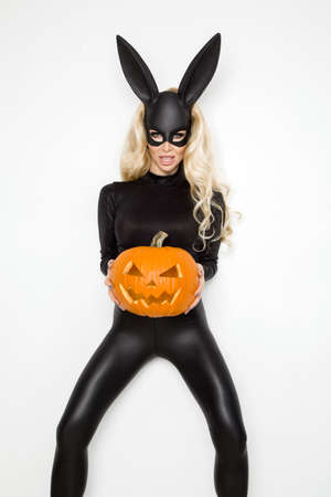 Beautiful young woman in halloween bunny costume, standing beside easter basket and holding pumpkin;