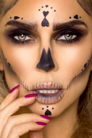 Sexy blonde woman in Halloween makeup on a beige background in the studio. Makeup artist skeleton, monster, witch.